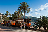 Spain, Balearic Islands, Majorca, Puerto Soller, the Orange Express tram dating of 1913 runningalong the coast than joining Soller after having crossed orange grove