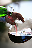 France, Vaucluse, Luberon, Lourmarin, labelled Les Plus Beaux Villages de France (The Most Beautiful Villages of France), la Feniere Inn, wine being poured in a carafe