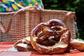 Brezel pretzel and picnic basket during hiking rest in forest, near Mespelbrunn, Raeuberland, Spessart-Mainland, Bavaria, Germany