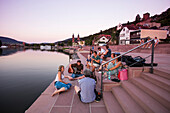 People sing, drink and relax on steps along riverfront of Main river at sunset, Miltenberg, Spessart-Mainland, Bavaria, Germany