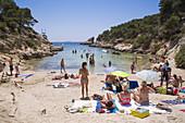 People relax on beach and swim at Cala Portals Vells bay, Portals Vells, Mallorca, Balearic Islands, Spain