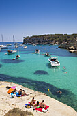 People relax on rocks with yachts and sailboats at anchor in Cala Portals Vells bay, Portals Vells, Mallorca, Balearic Islands, Spain