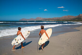 Two boys carry surfboards on beach along Bay of Alcudia, Colonia de Son Serra de Marina, Mallorca, Balearic Islands, Spain