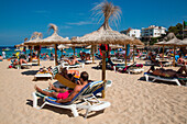 Young man and woman use smartphones while relaxing on beach, Portocolom, Mallorca, Balearic Islands, Spain