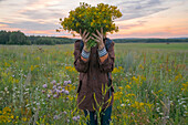 Caucasian woman holding bouquet of flowers over face in field at sunset