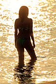 Silhouette of Mixed Race woman wading in ocean at sunset