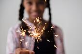 Mixed Race girl holding sparkler