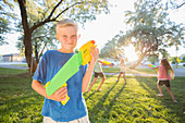 Caucasian boy posing with squirt guns