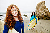 Smiling women holding surfboards at beach