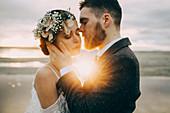 Caucasian bride and groom on sunny beach