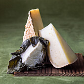 Variety of wedges of cheese on cutting board