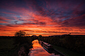 Barges lay still on the Shropshire Union canal as the dawn light sweeps across the sky above Beeston Castle, Cheshire, England, United Kingdom, Europe