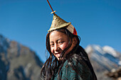 A Layap girl wearing a traditional hat smiles for the camera in the remote village of Laya, Bhutan, Asia