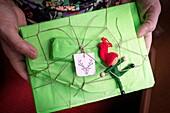 Manos de mujer sosteniendo y enseñando un paquete regalo de navidad color verde con una etiqueta con motivo navideño un cievo y un elf
