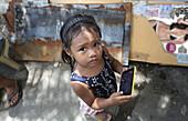 Street poverty, young girl with cellphone, Manila   Metro Manila