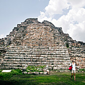 A young woman in a white shirt and tan shorts walks near a Mayan stone pyramid ruin near Merida, Mexico.