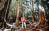 A young woman hiker in a bright orange jacket pauses on a steep trail surrounded by tall fir trees on a cold winter day.