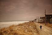 A female athlete on a training run along a road in the beach town of Hull, MA