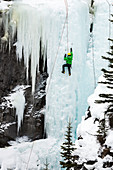 Male ice climber on frozen ice falls, Alberta, Canada
