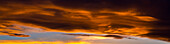 Panorama of colourful dramatic chinook arc cloud at sunset, Calgary, Alberta, Canada
