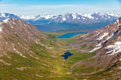 Aerial view of spring snow melting off the Kenai mountains on a clear summer day, Lost Lake in the valley below, Kenai Peninsula, Southcentral Alaska, Seward, Alaska, United States of America