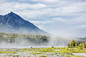 River silt being blown about Matanuska River bed on a windy and cloudy day, King Mountain in the background, south, central Alaska in summertime, Palmer, Alaska, United States of America