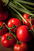 Bright red, ripe tomatoes with water droplets and green onions