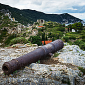 An old, rusted relic laying on the rock on a greek island with a rugged landscape and remote houses in the background, Skiathos, Greece