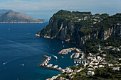 The rugged cliffs along the coastline of the island of Capri, and the town of Capri with a harbour, Capri, Campania, Italy