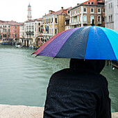 A person standing with a wet, colourful, umbrella looking out over a canal, Venice, Italy