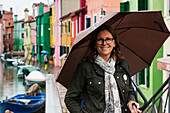 A woman stands beside a canal with an umbrella with colourful houses in a row in the background, Venice, Italy