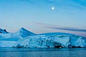 Full moon in a blue sky over the snow covered mountains and blue ocean, Antarctica