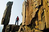 Hiker viewing the Balancing Rock and basalt rock cliffs, Long Island, Bay of Fundy, Nova Scotia, Canada