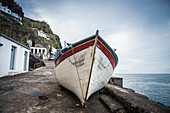 Fishing boat on the shore at the water's edge, Ponta do Arnel, Sao Miguel, Azores, Portugal
