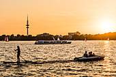 Boats and water sports enthusiasts on the lake Aussenalster at sunset, Hamburg, Germany