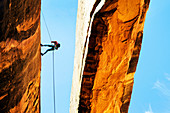 Rock climber using rope on arch