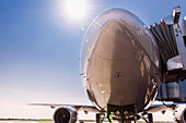 Low angle view of airplane at airport under blue sky