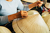 Close up of artisan weaving straw hat
