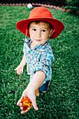 Caucasian boy wearing cowboy hat showing flowers in hand