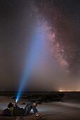 Asian man shining flashlight on starry sky