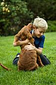 Caucasian boy hugging dog in grass