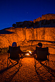 Caucasian couple holding hands near campfire at night