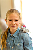 Caucasian girl with two pet birds standing on shoulder