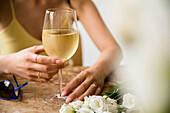 Hispanic woman drinking wine near flowers and sunglasses