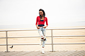 Black woman leaning on boardwalk railing