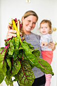 Smiling Caucasian mother holding daughter showing lettuce