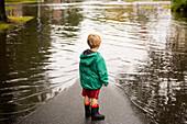 Caucasian boy wearing puddles near flood