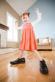 Caucasian girl wearing shoes of father in living room