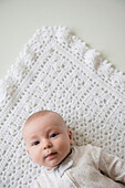 Caucasian baby laying on blanket