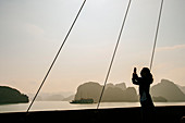Caucasian woman photographing rock formations in Ha Long Bay, Vietnam
